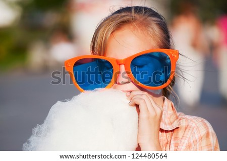 Teenage girl eating cotton candy - stock photo