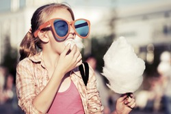 Teenage girl eating cotton candy outdoor