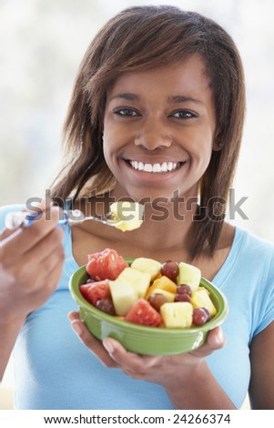 Teenage Girl Eating Fresh Fruit Salad
