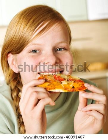 Teenage girl eating pizza