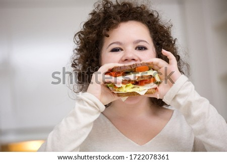 Teenage girl eating sandwich, portrait
