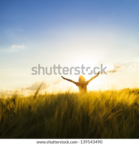 Teenage girl enjoy with sunshine in wheat field