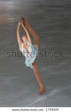 Teenage girl figure skating performance doeing a Bielmann.