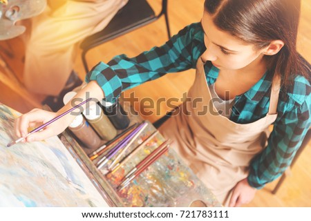 Teenage girl focusing on art canvas while painting