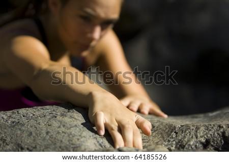 Teenage girl free rock climbing in summer