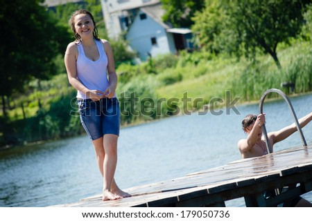 teenage girl having joyful time happy smiling & looking at camera on summer water outdoors background