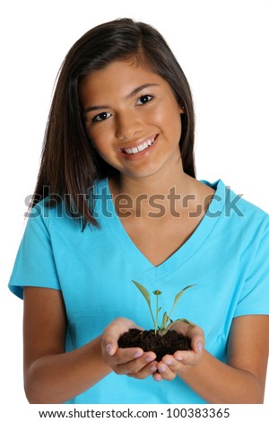Teenage girl holding a plant in dirt
