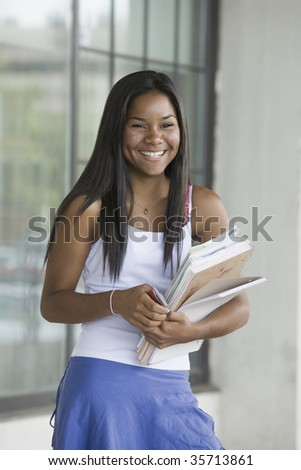 Teenage girl holding books and smiling in a school