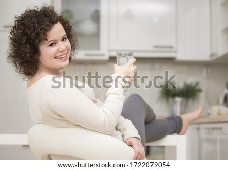 Teenage girl holding glass of water, portrait