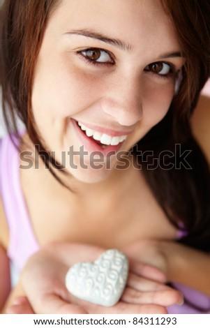 Teenage girl holding silver heart