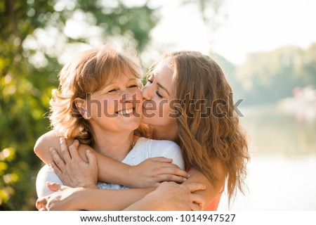 Teenage girl hugging and kissing her mother h outdoor in nature on sunny day