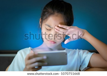teenage girl  hurt her eyes because she played the smart phone in the dark light  and the blue light has a negative effect on the child's eyes. #1070751668