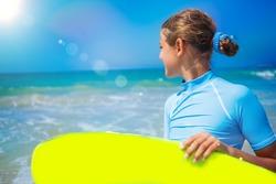 Teenage girl in blue has fun surfing
