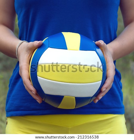 Teenage girl in blue shirt and yellow shorts holding a colorful sports ball for playing volleyball. Closeup Photo