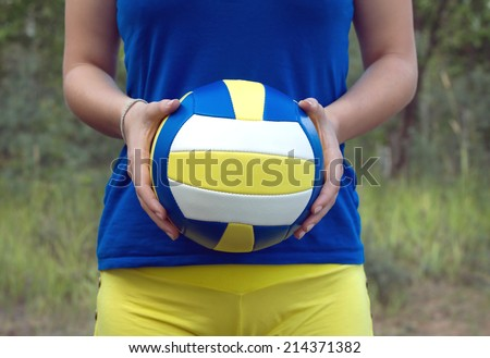 Teenage girl in blue shirt and yellow shorts holding a colorful sports ball for playing volleyball. Closeup Photo on blurred green background