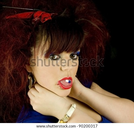 teenage girl in bright makeup and lipstick with pill on her tongue