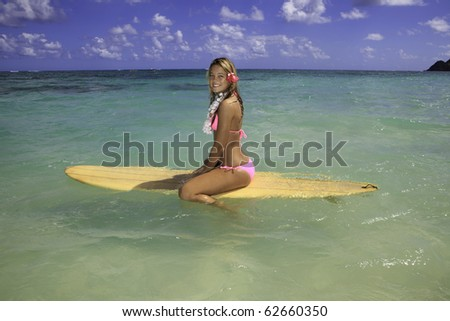 teenage girl in pink bikini at the beach in hawaii on her surfboard