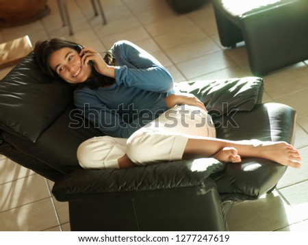 Teenage girl in reclining leather armchair at home using mobile phone ストックフォト ©