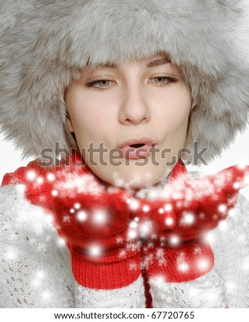 Teenage girl  in red gloves and fur hat blowing snow