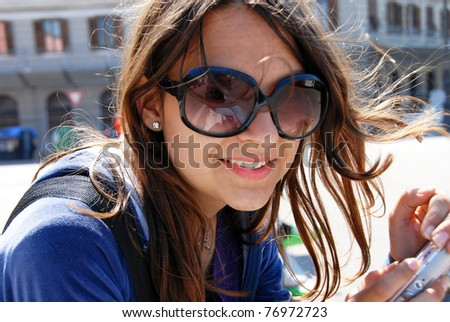 teenage girl in sunglasses with camera smiling outdoor
