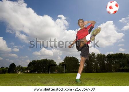 Teenage girl in uniform kicking soccer ball