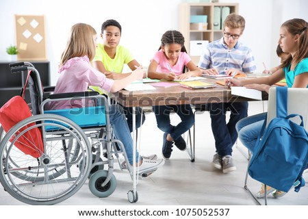 Teenage girl in wheelchair with classmates studying at school