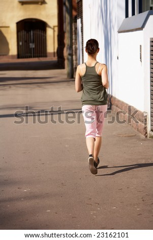 Teenage girl jogging away on sidewalk in city #23162101
