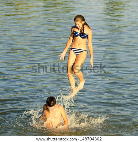 Teenage girl jumping into the river from boys shoulders.