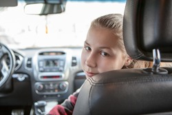 Teenage girl looking back from passenger front seat of car