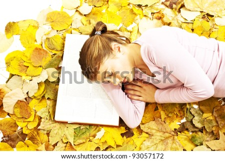 Teenage girl lying down reading book with leaves around