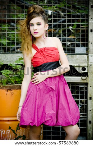 Teenage girl model presenting flashy clothes in old natural background