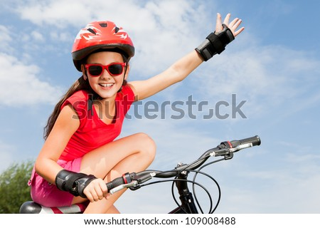 teenage girl on a bicycle with hand up