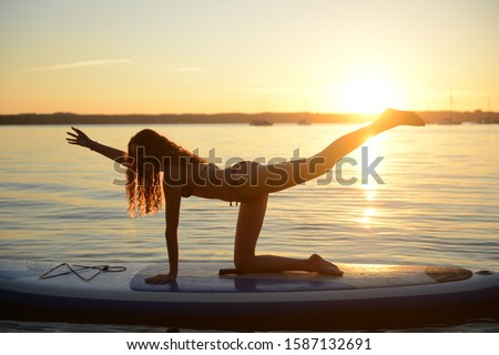 Teenage girl on paddleboard in yoga pose at sunset, Lake Starnberg, Bavaria, Germany, Europe