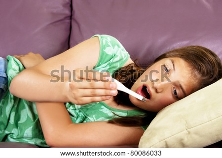 Teenage girl on sofa looking surprised at thermometer