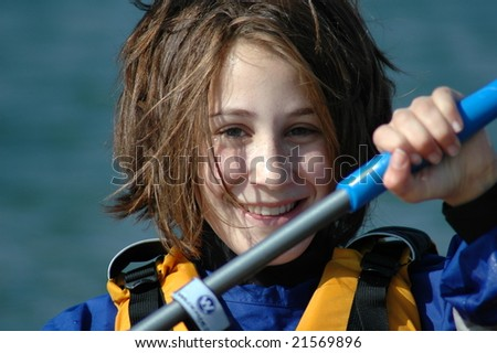 Teenage girl paddling a kayak on river