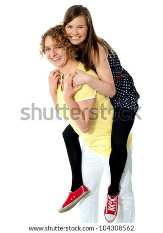 Teenage girl piggybacks her mother, studio shot