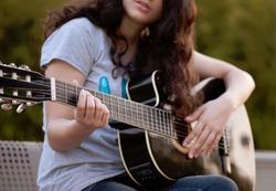 Teenage girl playing an acoustic guitar