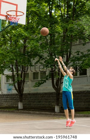 Teenage girl playing basketball shooting the ball at the hoop as she tries to score a goal