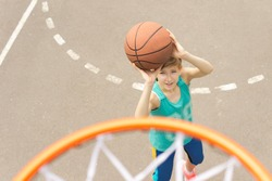 Teenage girl playing basketball taking aim at the goal with the ball raised in her hands, view from on top of the goalpost and net