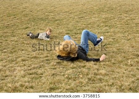 Teenage girl playing with her two year old brother outdoors
