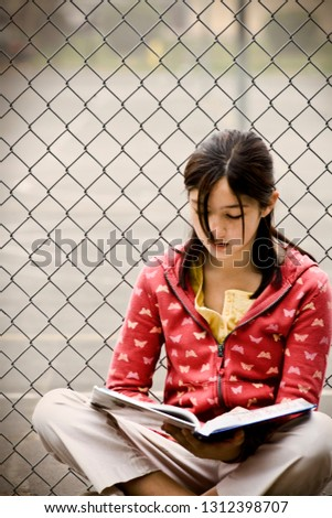 Teenage girl reading a book beside a wire fence.