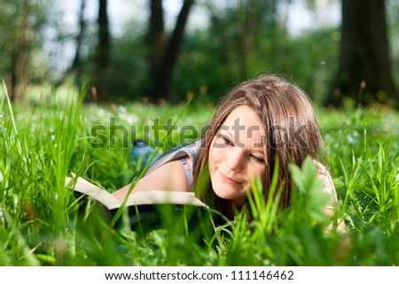 Teenage girl reading a book outdoors