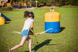 teenage girl running with bow and arrow during a game of archery tag