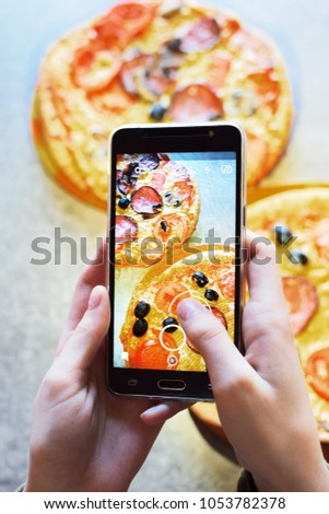 Teenage girl's hands with smartphone takes picture of fresh just baked hot selfmade pizza with salami, tomato, cheese, olives and mushrooms on grey grunge table background.