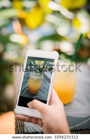 Teenage girl's hands with smartphone takes picture of lemon tea on table for social networks post in the garden