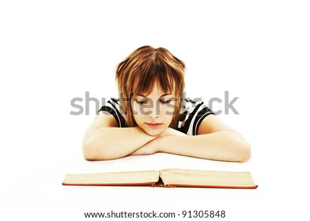 Teenage girl sitting at the desk and reading book. Isolated on white background