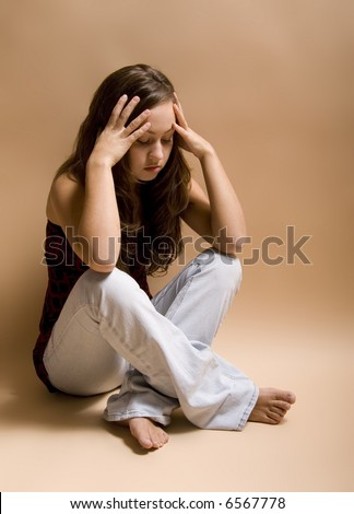 Teenage girl sitting cross-legged on floor in a depressed state.