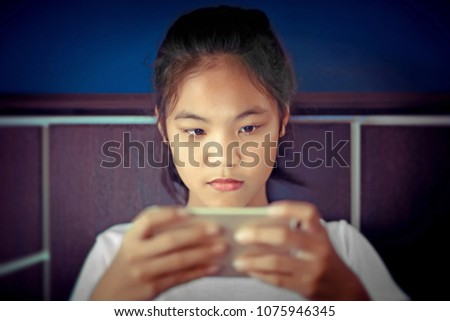 teenage girl sitting in bed  playing a smartphone in social internet  in the dark light under the blacket. The blue light has a negative effect on the child's eyes. #1075946345