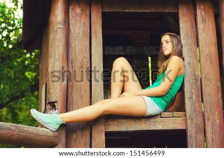 Teenage girl sitting in the wooden house up in the air.