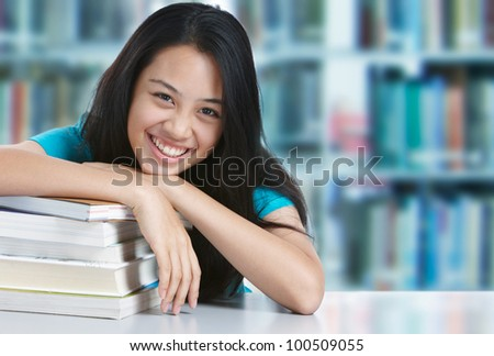 teenage girl smiling with stack of books in library - stock photo